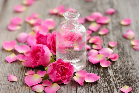 Essential oil with rose petals on wooden background Banque d'images