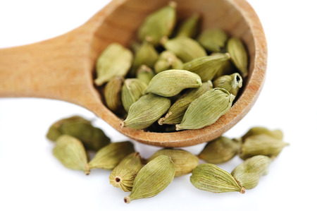 indian cookery: Cardamom seeds in the wooden spoon on white background