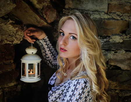pretty dress: Beautiful blond woman with a lantern against ancient stone wall