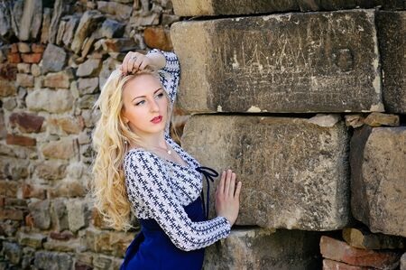 ancient sexy: Sexy blond woman leaning against ancient stone wall