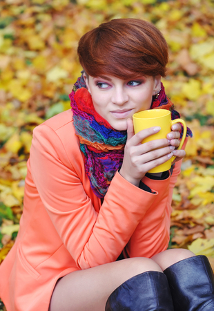 checkered scarf: Young beautiful woman holds the cup of tea in hands on a background autumn leaves Stock Photo