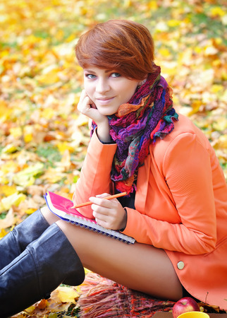 Red-haired student girl with notebook on a background of autumn leaves Banque d'images