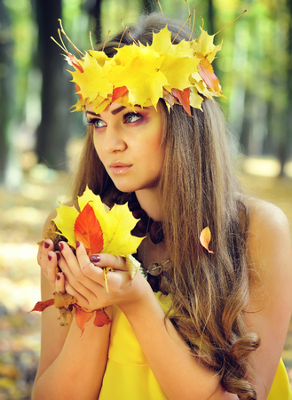 Portrait of a beautiful girl in a wreath of autumn leaves Stock Photo