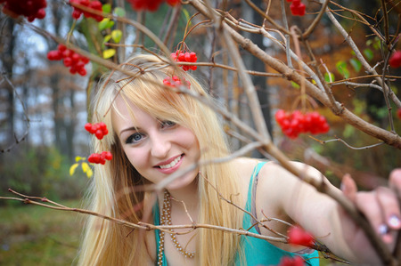 guelder rose berry: Portrait of a beautiful girl near the red viburnum