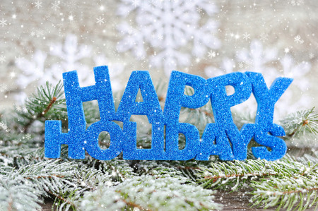holiday backgrounds: Inscription of happy holidays with spruce branches with frost Stock Photo