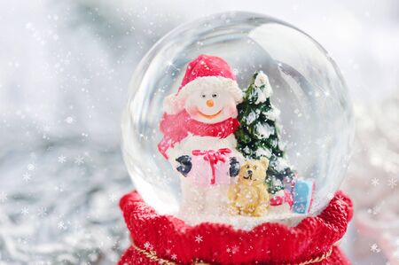 A snow globe with snowman on festive background Stock Photo