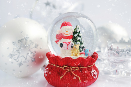 christmas snow: A snow globe with snowman and christmas decorations Stock Photo