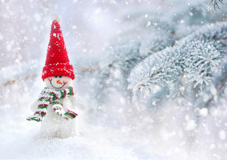 Snowman on a background snow-covered fir branches