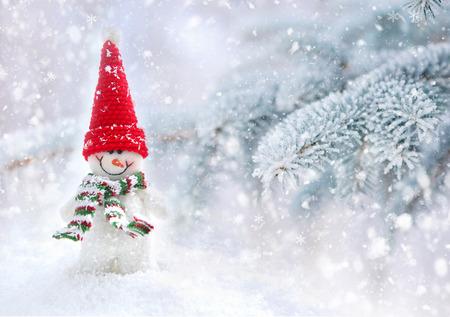 estaciones del a�o: Mu�eco de nieve en un fondo cubiertas de nieve las ramas de abeto