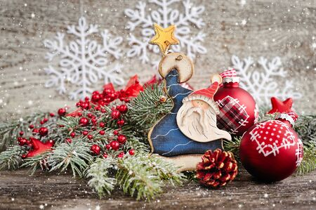 hristmas: Branches of fir with Santa Claus and Christmas decorations on wooden background
