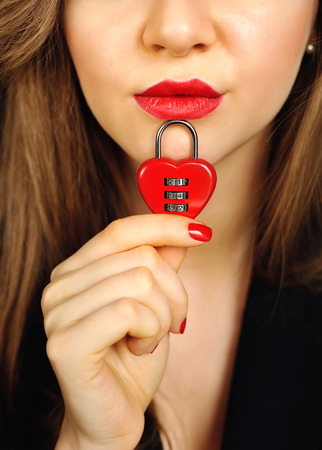 encoded: Beautiful girl with padlock heart-shape in hand