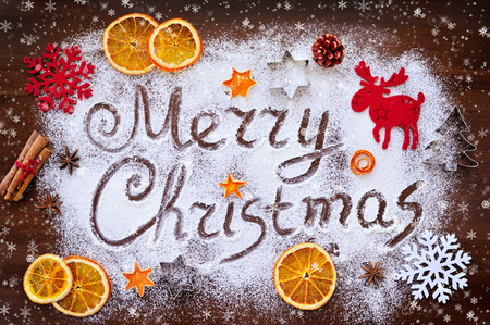 Merry Christmas text made with flour with decorations on cutting board