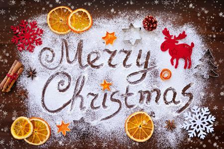 the christmas: testo Buon Natale fatto con farina con decorazioni a bordo di taglio Archivio Fotografico