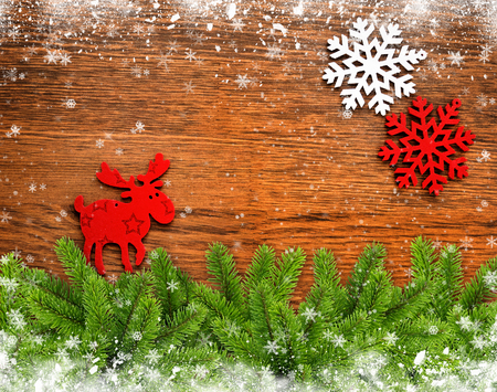christmas elk: Christmas figurine elk, snowflakes and Christmas tree branches on a wooden background