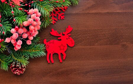 christmas elk: Christmas figurine elk and spruce twigs on a wooden background Stock Photo