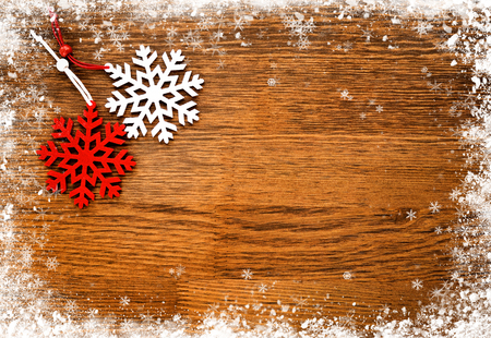 Red and white snowflake on a wooden snowy background