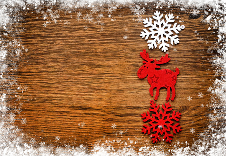 christmas elk: Christmas figurine elk and snowflakes on a wooden snowy background