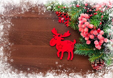christmas elk: Christmas figurine elk and spruce twigs on the snow-covered wooden background
