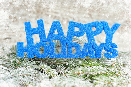 happy holidays: Inscription of happy holidays with spruce branches with frost Stock Photo