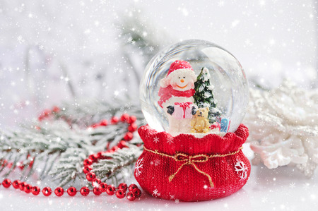 glass christmas tree ornament: A snow globe with snowman on background spruce branches with snow