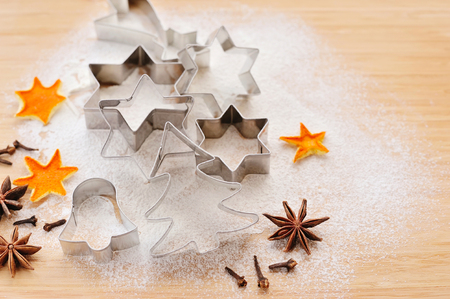 metal christmas cookie cutters in freshly sifted flour on wooden chopping board stock photo 49527196 - Metal Christmas Cookie Cutters