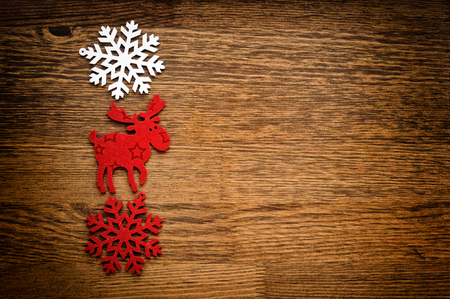 christmas elk: Christmas figurine elk and snowflakes on a wooden background Stock Photo