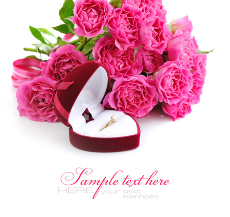 jewel case: Red velvet box with golden ring and bouquet of pink roses on a white background