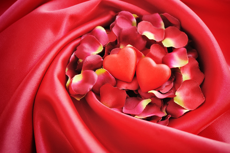 love rose: Two hearts on a background of red petals and satin