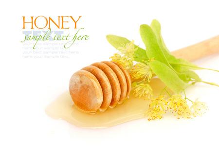 Dipper met honing met bloemen van linden op een witte achtergrond Stockfoto