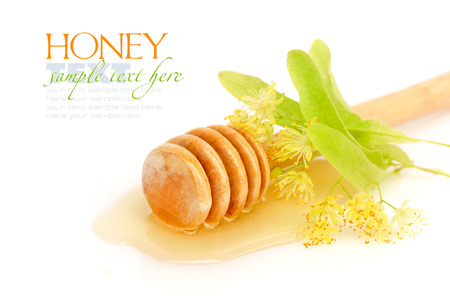 Honey dipper with honey with flowers of linden on white background