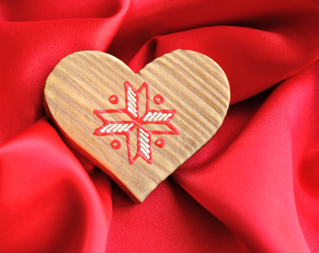satin background: Wooden Heart on red satin background