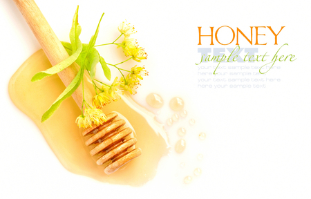 Honing dipper met honing met bloemen van linden op witte achtergrond Stockfoto