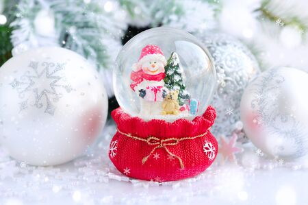christmas hats: A snow globe with snowman on background spruce branches with snow