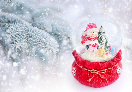 snowcovered: A snow globe with snowman on a background snow-covered fir branches Stock Photo