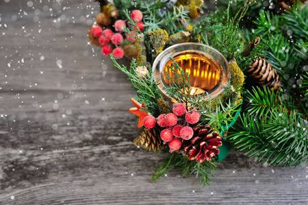 tree decorations: Candlestick and Christmas tree branches on a wooden table. Natural Christmas Decor