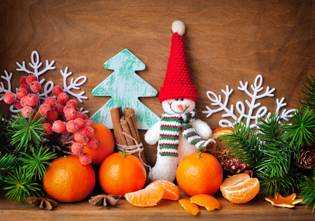 Snowman with tangerines and branches of fir and Christmas decorations on a wooden background