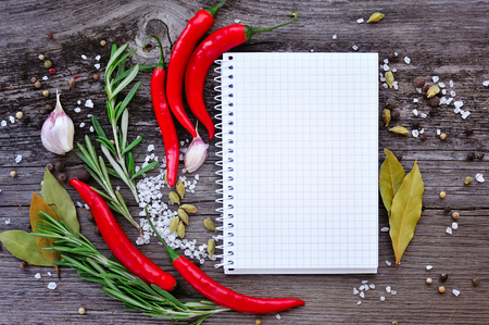 seasonings: Vegetables and seasonings with open notebook for recipes on a wooden background Stock Photo