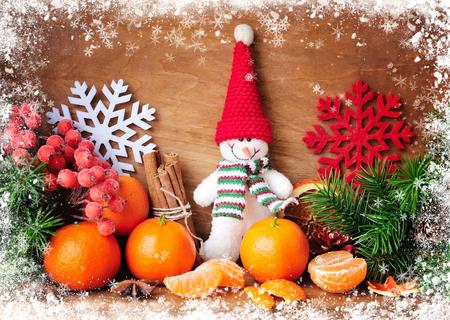 みかんとモミと木製の背景のクリスマスの装飾の枝と雪だるま
