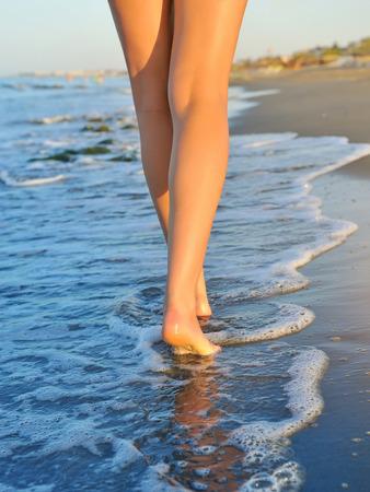 Mooie vrouw benen, wandelen op het strand