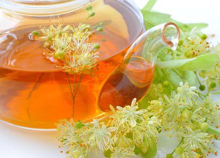 linden tea: Teapot with linden tea and flowers, close-up Stock Photo