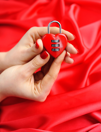 lockout: Padlock heart-shape in womens hands against a background of red silk