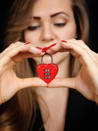 lockout: Beautiful girl with padlock heart-shape in hands Stock Photo