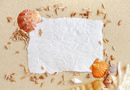 hoja en blanco: conchas de mar, papel de la vendimia con la arena como fondo Foto de archivo