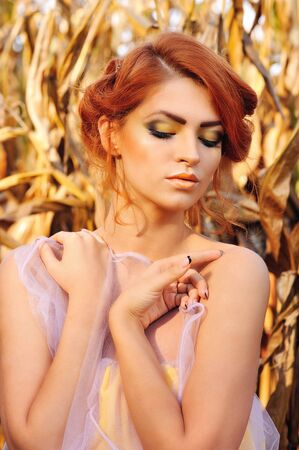 beautiful redhead: Beautiful redhead woman posing over corn autumn field Stock Photo