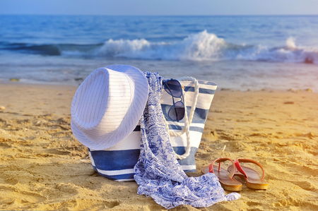 Hat, bag, sun glasses and flip flops on a sandy beach. Summer vacation concept Stock Photo
