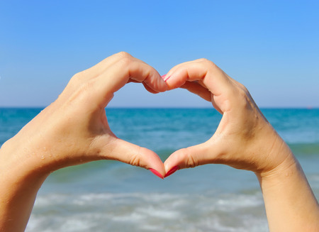gesticulation: Female hands in the shape of heart on the background sea