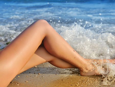 nude sexy woman: Sexy female legs in the waves of the surf