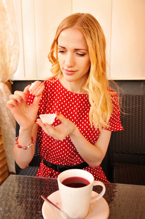 teaparty: Beautiful blond woman eating macaroon while having tea-party. Shot in the cafe Stock Photo