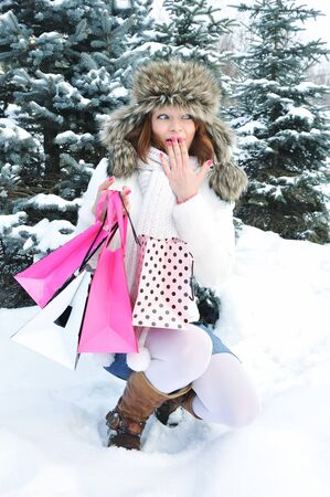 Beautiful happy girl with shopping bags in a winter park