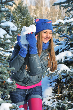 snowballs: Winter woman play snowballs on snow background